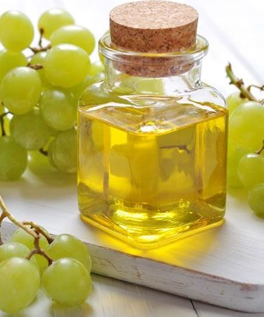 grape seed oil in glass with grapes