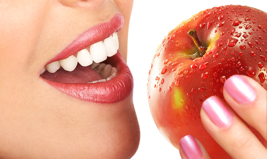 5 Useful Nutritional Strategies for Healthy Teeth and Gums_woman eating an apple