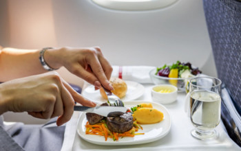 Fly Gluten-Free With These Airlines_Woman-eating-steak-on-an-airplane